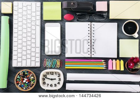 Top view of wooden office table with blank white smartphone keyboard clock notepad coffee cup and other items organized in a neat and creative manner. Mock up