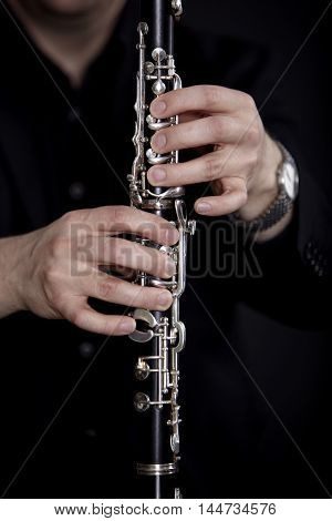 Clarinet player in front of black background