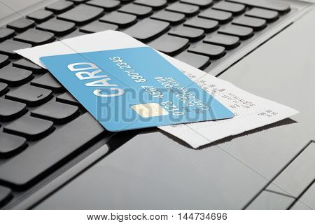 Credit card and receipt over computer keyboard as symbol of online shopping