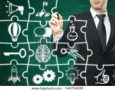 Businessman drawing business icons on abstract puzzle pieces. Chalkboard background