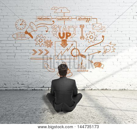 Startup concept with businessman sitting on concrete floor and looking at orange sketch drawn on white brick wall