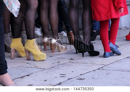 Women legs in a crowded place - closeup of people shoes