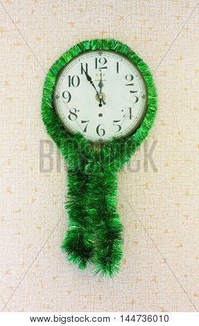 five minutes to twelve on old wall clock decorated with green tinsel. concept of New Year Christmas