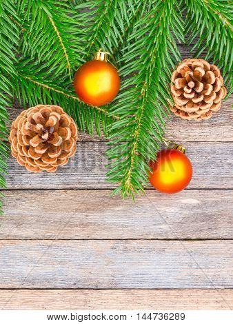 New Year or Christmas background: fir branches goldish glass balls cones over old wooden backdrop top view copy space