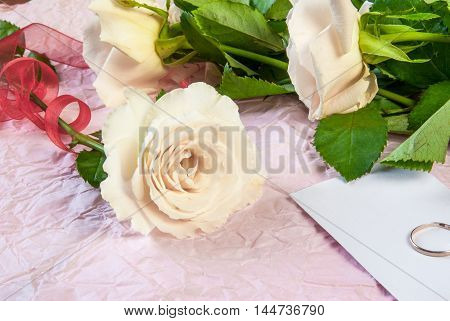 pink rose on a pink textured paper background. Romantic mood. One rose wrapped festive ribbon. Preparing for the proposal: next to the rose note and ring. Copy space