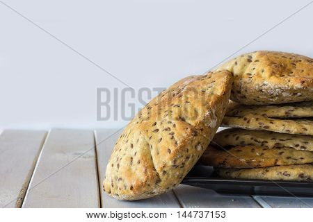 Wholemeal Pita Bread Stacked on Plate on White Wooden Table Horizontal