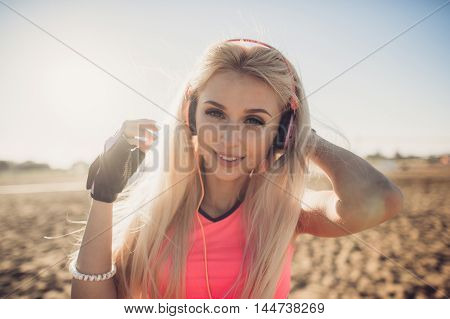 Success fitness woman concept with sports armband and earphones. Winning concept of female athlete runner cheering with arms raised up for achievement in weight loss or life goal