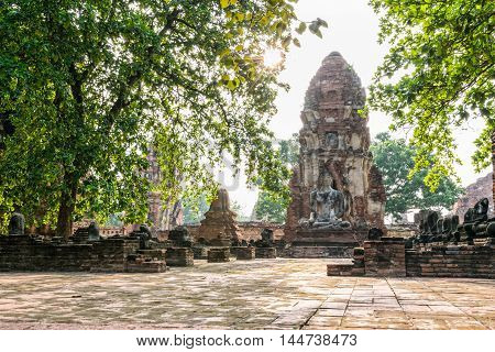 Buddha statue sitting position at front of pagoda under sun light surround by trees and ancient ruins of Wat Phra Mahathat temple in Phra Nakhon Si Ayutthaya Historical Park Thailand