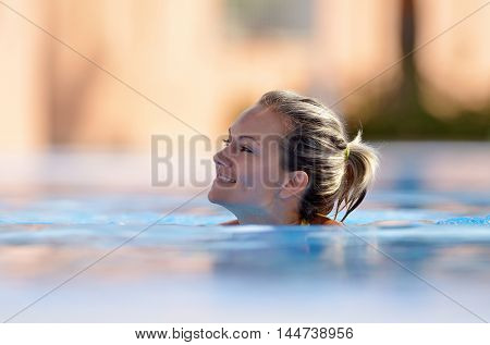 young woman swimming in the pool on warm summer day