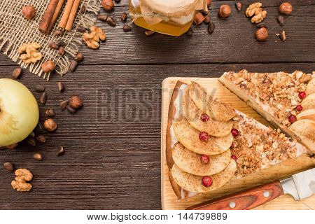 Homemade pie covered with apples, cinnamon, foxberry and nuts on the dark wood table