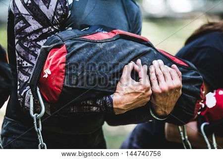 Close-up of man training at crossfit center with sandbag.
