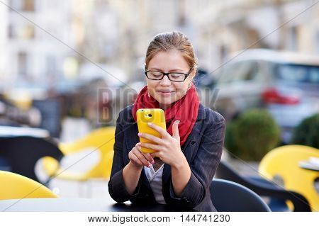 young woman in glasses writes sms on phone.