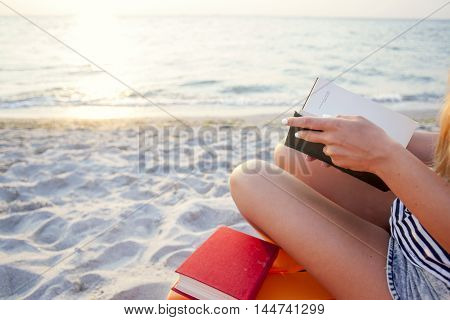 Woman reading book relaxed in deck chair. Seaview. Copy space for text.