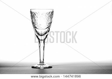 Empty wineglass of crystal over white background