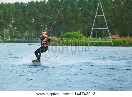 Cable wakeboarding- man riding a board on water surface