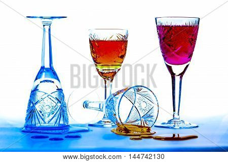 Wineglasses of cut-glass full of colorful liquids over white and blue background