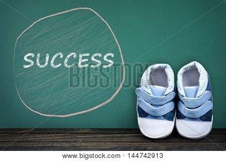 Success text on school table and kid shoes