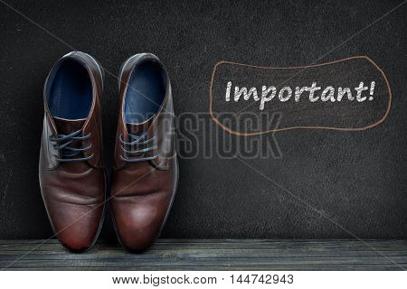 Important text on black board and business shoes on wooden floor