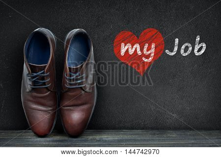 Love my job text on black board and business shoes on wooden floor