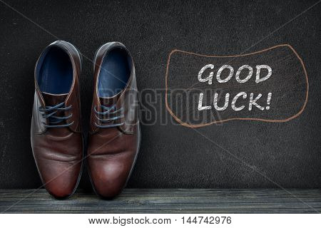 Good luck text on black board and business shoes on wooden floor