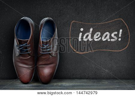 Idea text on black board and business shoes on wooden floor