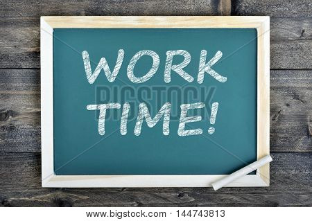 Work Time text on school board and chalk on wooden table