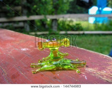 Glass toy frog in the sun on the forest glade
