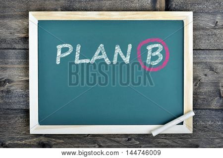 Plan B text on school board and chalk on wooden table