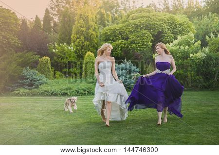 Bride and bridesmaid outside. Two beautiful girls running on lown. Bride in wedding dress. Bridesmaid in a purple evening gown. Hair fluttering in the wind