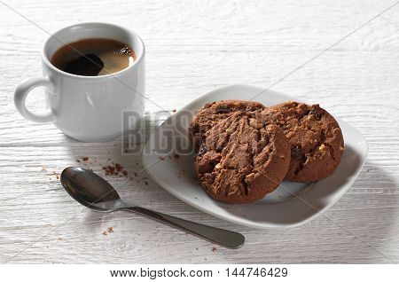 Cup of coffee with chocolate cookies on white wooden table