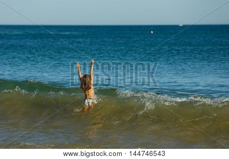 ALBUFEIRA, PORTUGAL - AUGUST 20, 2016: girl at the famous beach of Olhos de Agua in Albufeira. This beach is a part of famous tourist region of Algarve.