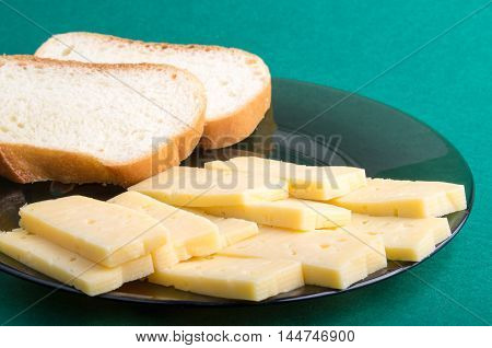 Plate On A Green Background With Cheese Slices And Pieces Of Bread