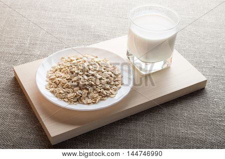 Saucer Of Cereal And A Glass Of Milk In The Backlight