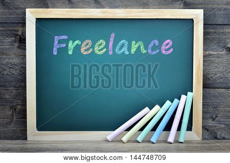 Freelance text on school board and chalk on wooden table