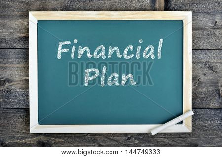 Financial Plan text on school board and chalk on wooden table