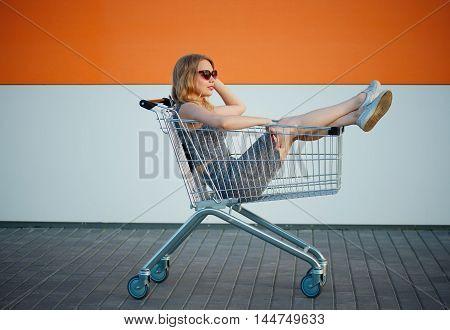 young beautiful blonde girl sitting in shopping basket