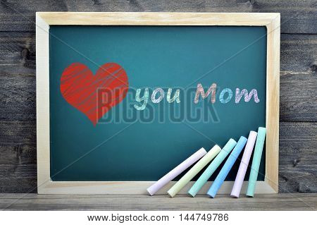 Love mom text on school board and chalk on wooden table