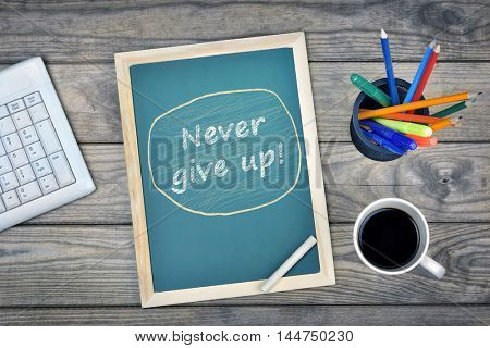 Never give up text on school board and coffee on desk