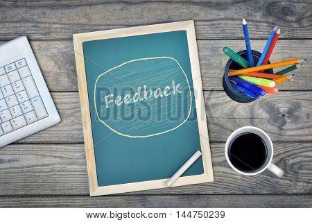 Feedback text on school board and coffee on desk