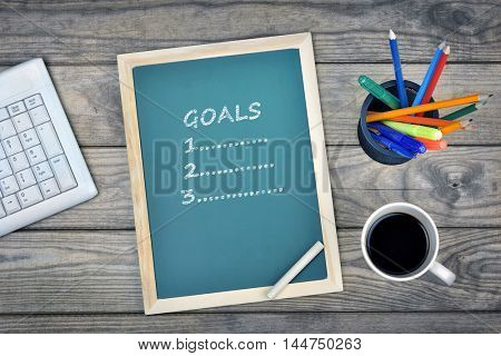 Goals text on school board and coffee on desk