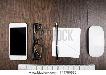 Closeup of wooden office desktop with blank cellphone glasses piece of paper with pen computer mouse and keyboard. Top view Mock up