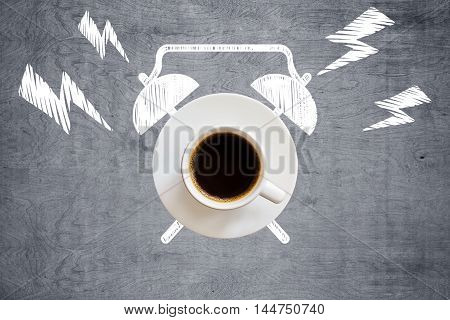 Top view of ringing coffee cup alarm clock sketch on grey wooden desktop. Time management concept