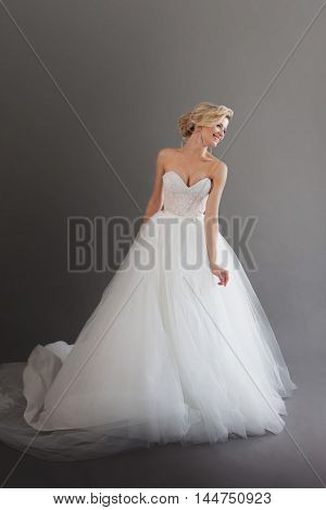 Charming young bride in luxurious wedding dress. Pretty girl in white. Emotions of happiness, laughter and smile, gray background