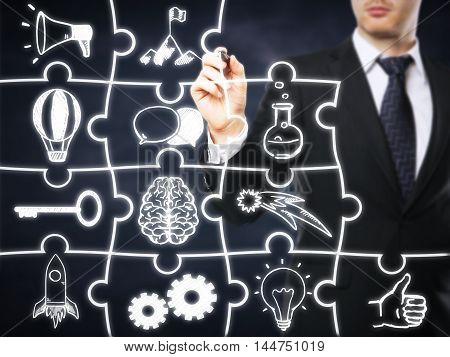 Businessman drawing business icons on abstract puzzle pieces. Blackboard background