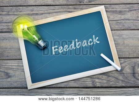 Feedback text on school board and glowing light bulb