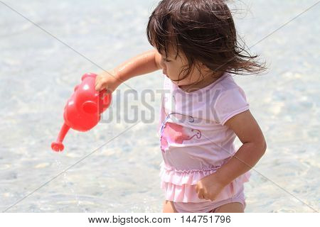 Japanese girl playing with water with watering pot (1 year old)
