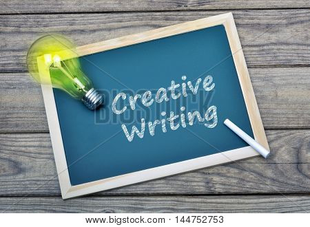 Creative Writing text on school board and glowing light bulb