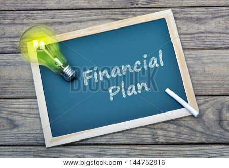Financial Plan text on school board and glowing light bulb