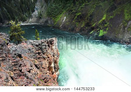 Rushing water from Upper Falls rounds a bluff of rocks on its way to Lower Falls in the