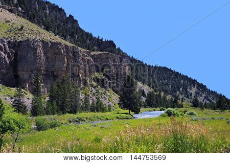 Rocky bluffs overlook the Gallatin River as it twists and turns. Grassy meadow runs up to edge of river.